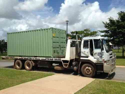 Tilt tray truck with container on it