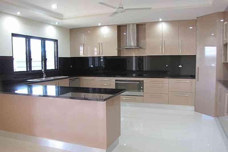 Beige kitchen with black bench and backsplash